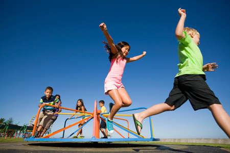 elementary age boy: Children jumping off merry-go-round at playground