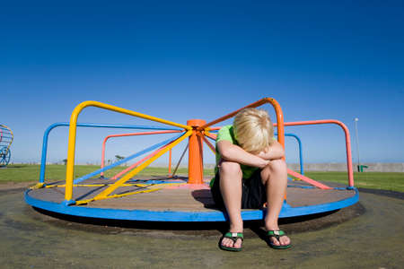frustrating: Frustrated boy sitting on still merry-go-round at playground