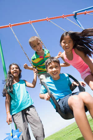 swing set: Children smiling together at swing set on playground LANG_EVOIMAGES