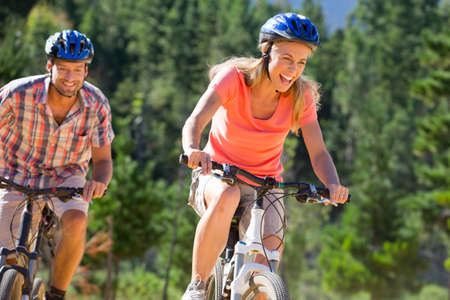 transportation: Couple riding mountain bikes in forest