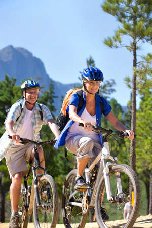 all weather: Older couple riding mountain bikes in forest