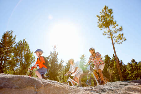 three generations: Three generations of men riding mountain bikes in forest LANG_EVOIMAGES