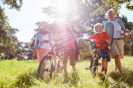 Grandparents and grandchildren pushing mountain bikes in rural field Stock Photo