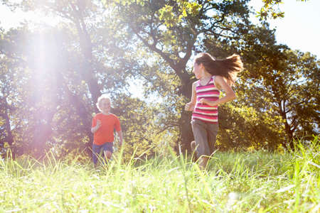 level playing field: Children running in rural field