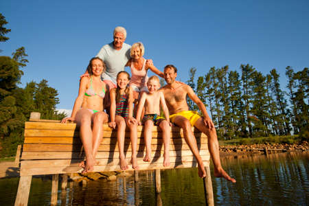 wooden dock: Multi-generation family sitting on wooden dock at lake LANG_EVOIMAGES