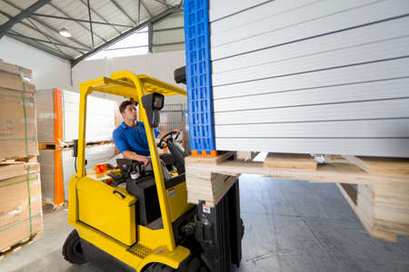 truck driver: Forklift truck driver worker stacking panels in solar panel factory warehouse LANG_EVOIMAGES