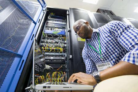 server farm: Technician with laptop checking server in data centre
