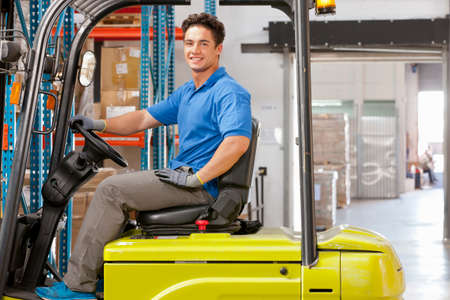 truck driver: Portrait of Forklift truck driver smiling at camera stacking boxes in warehouse LANG_EVOIMAGES