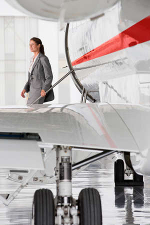 exiting: Businesswoman exiting on stairs of private jet