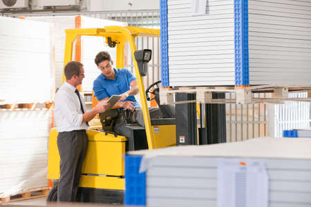 truck driver: Businessman supervising forklift truck driver in solar panel factory warehouse