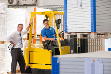 truck driver: Businessman smiling at camera supervising forklift truck driver in solar panel factory warehouse