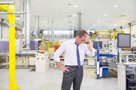 linea de produccion: Frustrado propietario de negocios con la cabeza en las manos sobre la l�nea de producci�n de la f�brica baja LANG_EVOIMAGES