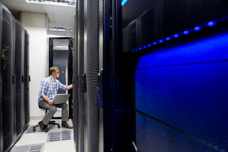colocation: Technician with laptop checking server in data centre
