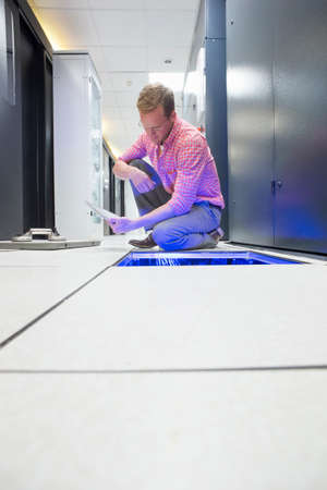 Technician with digital tablet checking cabling under floor of data centre server room