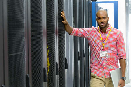 it technician: Technician looking at camera with laptop in server data centre