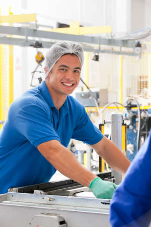 Portrait of Technician worker smiling at camera in solar panel factory production line