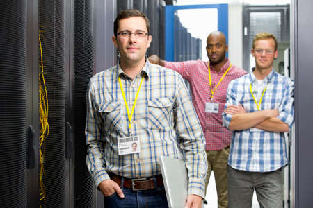 colocation: Technicians with laptop looking at camera in data centre server hall LANG_EVOIMAGES
