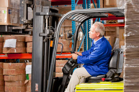 stacking: Worker driving forklift stacking boxes in warehouse LANG_EVOIMAGES