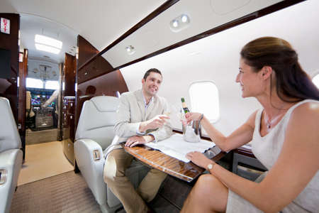 private airplane: Smiling couple making a toast with champagne in private jet LANG_EVOIMAGES