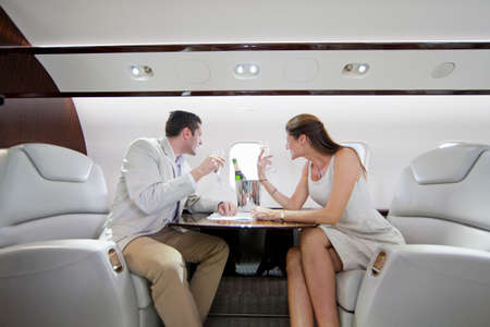 private airplane: Smiling couple drinking champagne and looking out of window in private jet