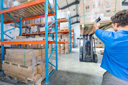 overseeing: Worker directing forklift truck in factory warehouse