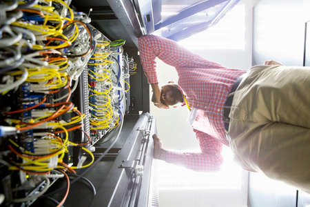 colocation: Frustrated technician checking wiring of server in data centre