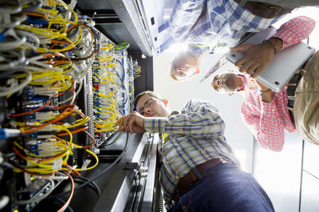colocation: Technicians with laptop checking wiring of server in data centre LANG_EVOIMAGES