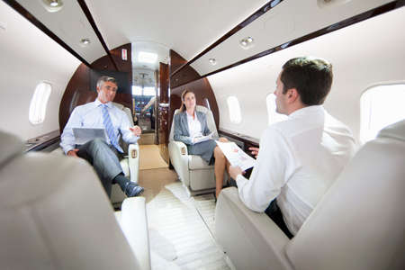 Businessmen and Businesswoman with digital tablet having meeting in private jet