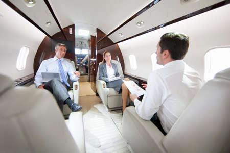 chorro: Hombres de negocios y empresaria con la tableta digital que tiene reunión en jet privado