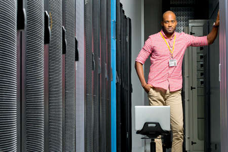 colocation: Technician with laptop looking at camera in server data centre