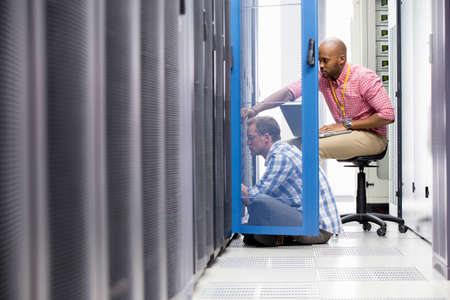 Technicians with laptop checking server in data centre Stock Photo