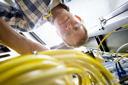colocation: Technician checking wiring of server in data centre