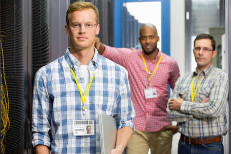 Technicians with laptop looking at camera in data centre server hall Stock Photo