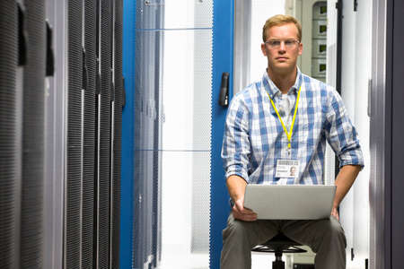 Technician with laptop looking at camera and checking server in data centre Stock Photo