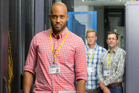 colocation: Team of technicians looking at camera in server data centre