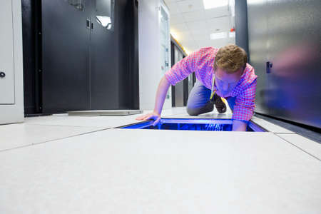 colocation: Technician checking cabling under floor of data centre server room