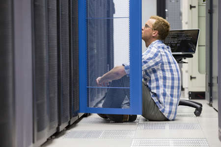 Technician with laptop looking at server in data centre
