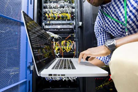 network engineer: Technician with laptop checking server in data centre