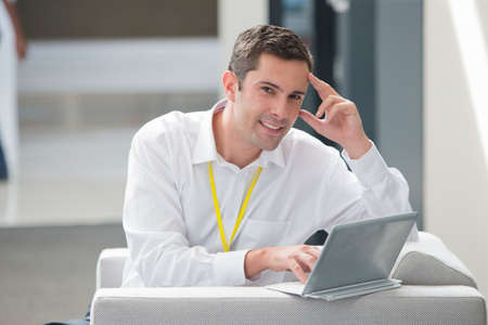 Businessman sitting on sofa in office working on digital tablet smiling at camera Stock Photo