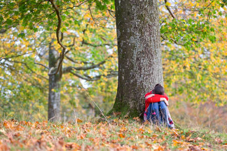 Young girl,looking sad,leaning against tree,in autumnal park