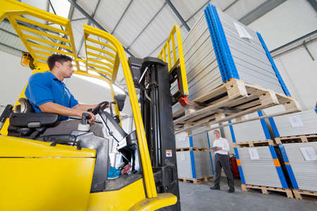 truck driver: Businessman supervising forklift truck driver worker in solar panel factory warehouse LANG_EVOIMAGES