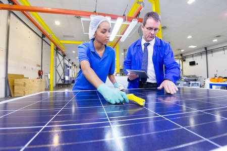 Supervisor worker overseeing Technician cleaning new solar panel in factory