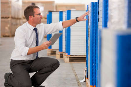 Businessman checking solar panels with digital tablet in factory warehouse Stock Photo