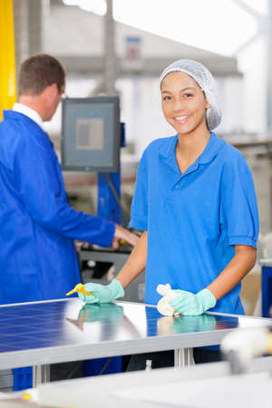 Technician worker smiling at camera cleaning and checking newly manufactured solar panels on production line LANG_EVOIMAGES