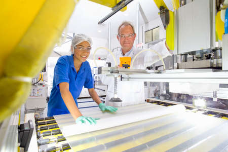 supervisión: Engineer smiling at camera checking worker coating solar panel glass on production line on factory floor LANG_EVOIMAGES