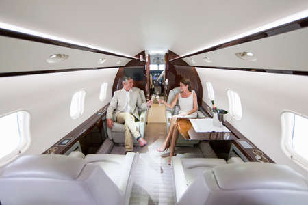 prestigious: Smiling couple making a toast with champagne in private jet LANG_EVOIMAGES