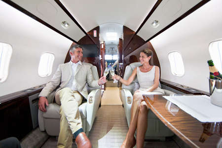 Smiling couple making a toast with champagne in private jet Stock Photo