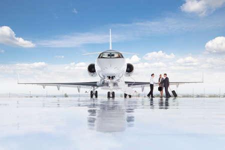 prestigious: Pilot greeting businessman and businesswoman boarding private jet