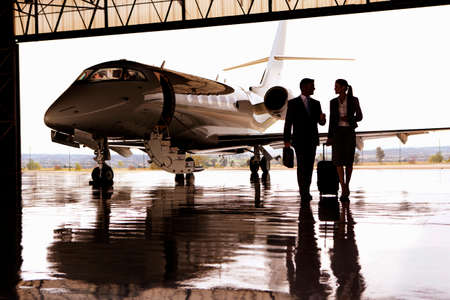 Silhouette of Businessman and Businesswoman walking away from private jet in hangar Stock Photo