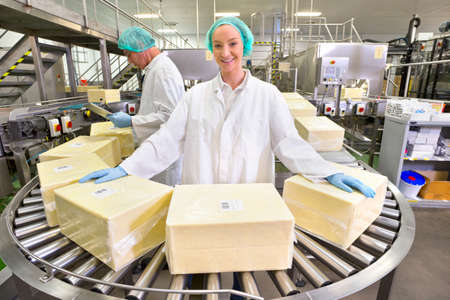 woman handle success: Portrait confident worker handling large blocks of cheese at production line in processing plant LANG_EVOIMAGES